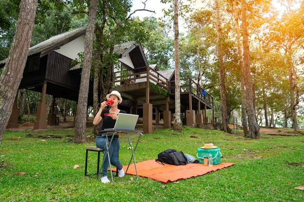 Kobiety pije kawę rano i pracuje na laptopie w urlopowym wakacyjnym czasie