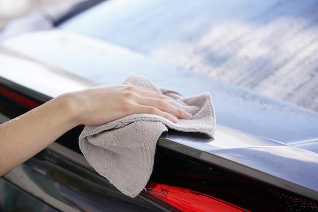 Kobiety po suchym czyszczeniu przecierają powierzchnię samochodu ściereczką z mikrofibry.