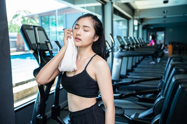 Kobiety po treningu wytrzyj twarz białą szmatką na siłowni.