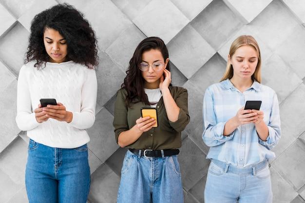 Kobiety pod dużym kątem korzystające z telefonów komórkowych