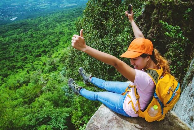 Kobiety podróżujące po azji relaksują się w czasie wakacji. usiądź na klifie. na moutain.