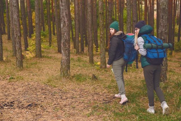 Kobiety podróżujące z powrotem w lesie sosnowym.