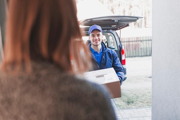 Kobiety powitania deliveryman na ganeczku