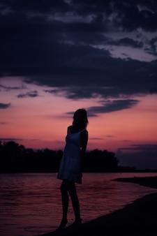 Kobiety pozują na tle wody i zachodu słońca szczupła młoda kobieta stoi w letniej...