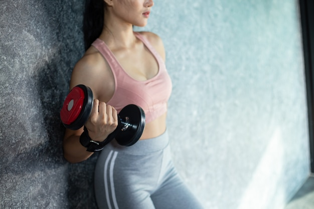 Kobiety pozycja ćwiczy z czerwonym dumbbell w gym.
