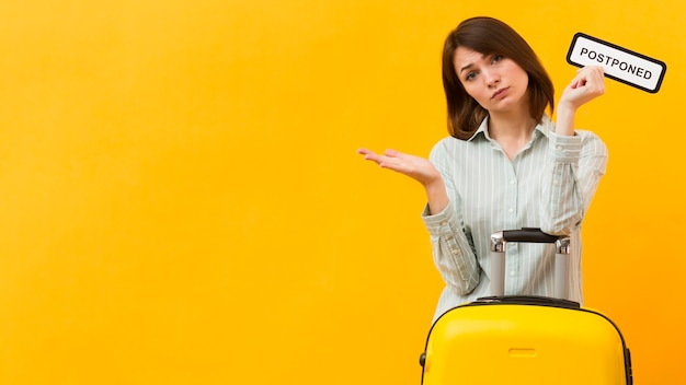 Kobiety pozycja obok jej bagażu podczas gdy trzymający przełożonego znaka z kopii przestrzenią