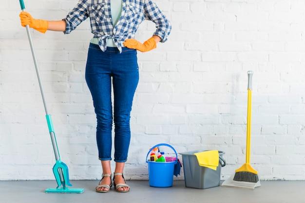 Kobiety pozycja przed ściana z cegieł z cleaning equipments