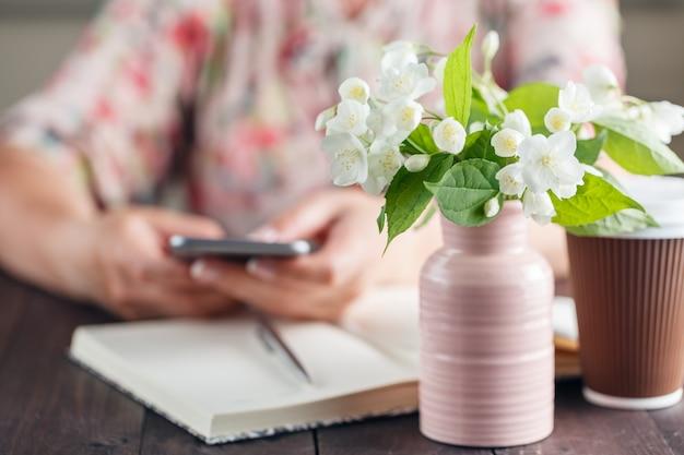 Kobiety praca przy stołem z kwiatu bukietem ana zabiera kawę