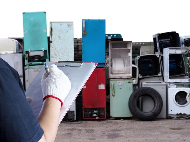 Kobiety pracują w recyklingu elektroniki śmieciarki odpady z pralki stare, używane i przestarzałe urządzenia elektroniczne do recyklingu w przemyśle fabrycznym.