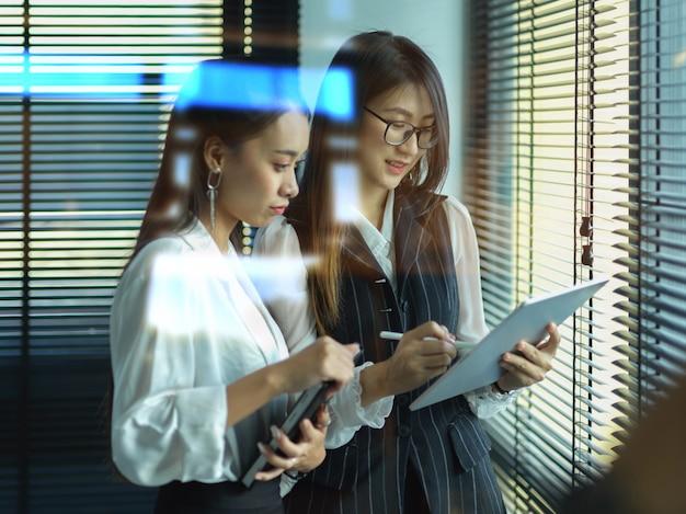 Kobiety pracujące w biurze konsultują się ze swoim projektem stojąc w biurze
