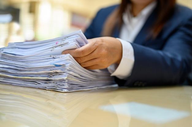 Kobiety pracującej udaje się znaleźć dokumenty biurowe