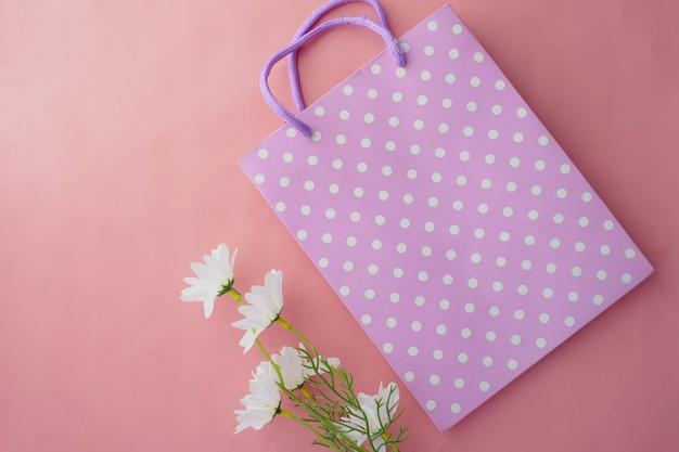 Kobiety prezent torba na różowym tle widok z góry.