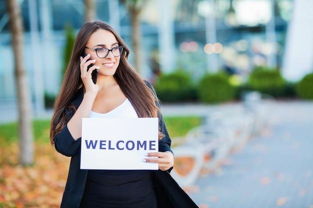 Kobiety prowadzą interesy z plakatem z wiadomością powitalną