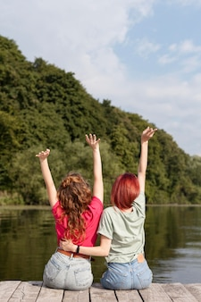Kobiety przebywające na doku z rękami w powietrzu