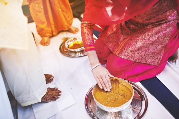 Kobiety przygotowujące się do wklejenia oleju z kurkumy (haldi) zmieszanego z mlekiem u stóp panny młodej