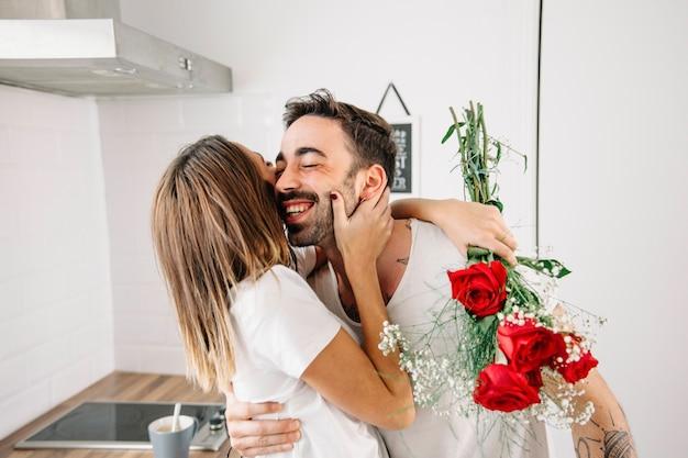 Kobiety przytulenia mężczyzna po tym jak otrzymywający bukiet