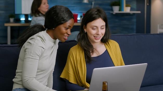 Kobiety rasy mieszanej cieszą się czasem spędzanym razem oglądając film na laptopie, relaksując się na kanapie. w tle kobieta i mężczyzna pijący piwo, towarzysko późno w nocy podczas imprezy relaksacyjnej