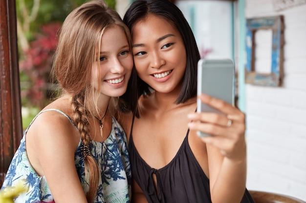 Kobiety rasy mieszanej mają prawdziwą przyjaźń, pozują do robienia selfie w nowoczesnej kawiarni. wieloetniczne młode kobiety używają telefonu komórkowego do robienia zdjęć