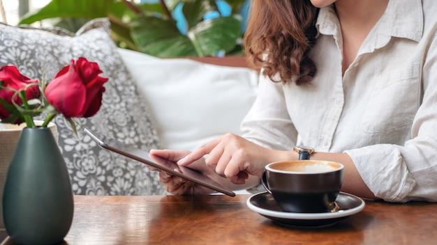 Kobiety ręce trzymając i wskazując na czarny tablet pc z filiżanką kawy na drewnianym stole w kawiarni