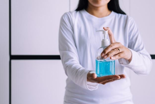 Kobiety ręce trzymając żel dezynfekujący w butelce z pompką do ochrony koronawirusa higieny rąk w sypialni