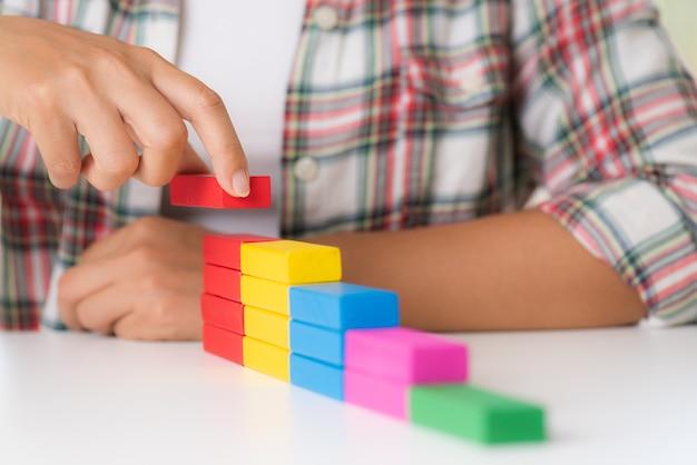 Kobiety ręcznie układają kolorowe drewniane klocki w kształcie klatki schodowej