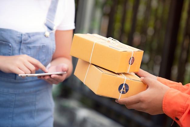 Kobiety ręka akceptuje doręczeniowych brown pudełka od deliveryman dostawy pojęcia