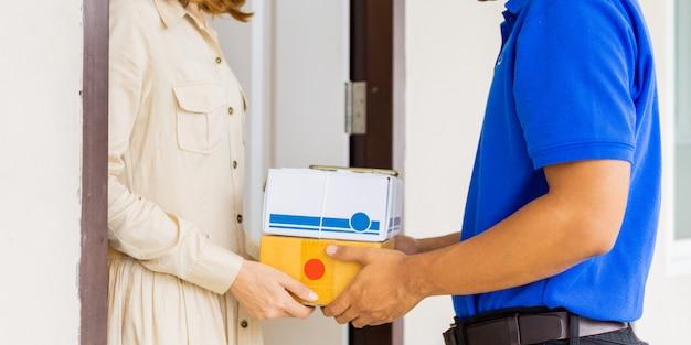 Kobiety ręka akceptuje dostawę pudełka od deliveryman w błękitnych mundurach przy drzwi.