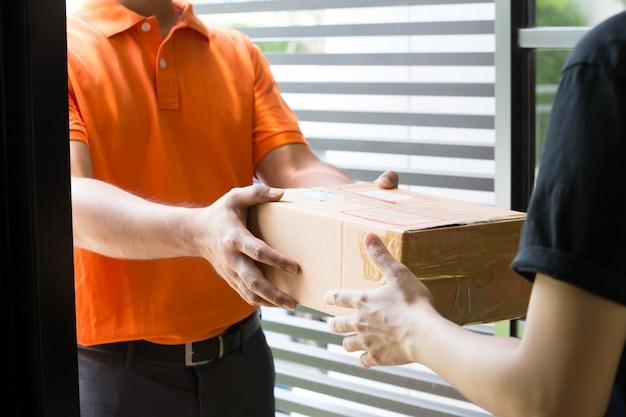 Kobiety ręka akceptuje dostawę pudełka od deliveryman