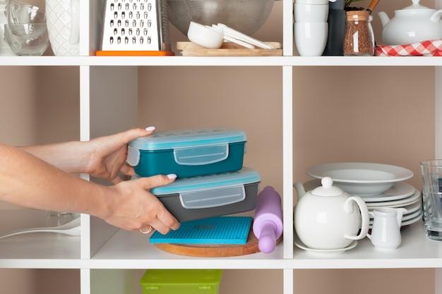 Kobiety ręka bierze dishware kawałki od półki w kuchni