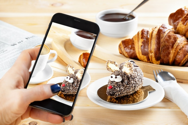 Kobiety ręka bierze telefon fotografię jedzenie. śniadanie kontynentalne z rogalikami, ciastem w postaci myszy i kawy. fotografia na smartfony dla mediów społecznościowych, blogowanie.