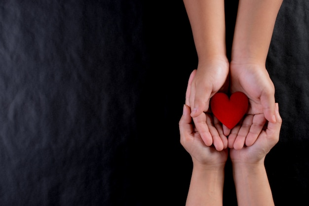Kobiety ręka daje czerwonemu sercu dziecko. międzynarodowy dzień koncepcji charytatywnej. skopiuj miejsce