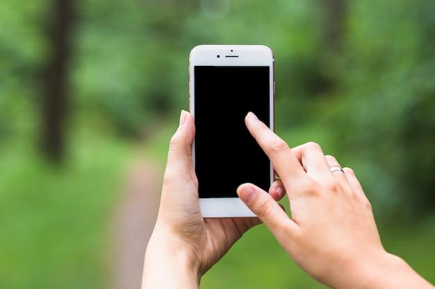 Kobiety ręka dotyka mobilnego ekran przy outdoors