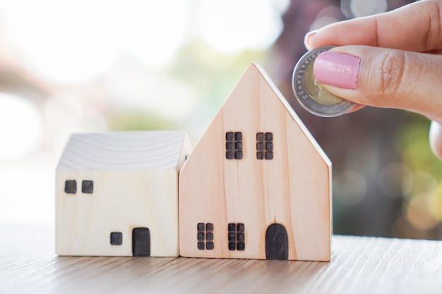 Kobiety ręka oszczędza pieniądze w domowym prosiątko banku