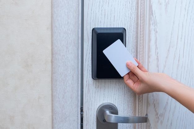 Kobiety ręka otwiera hotelowego drzwi z kartą