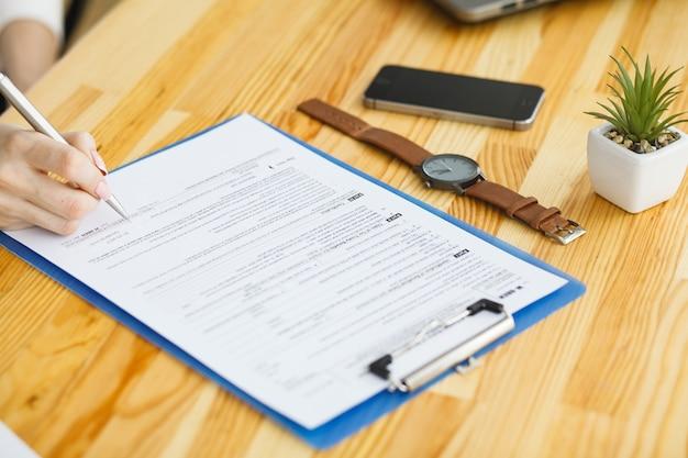 Kobiety ręka pisze lub podpisuje wewnątrz dokument