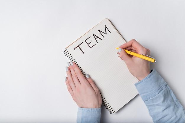Kobiety ręka pisze w notatnika słowie zespół