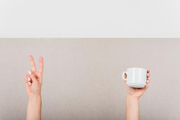 Kobiety ręka robi zwycięstwo znakowi i biała filiżanka przeciw ścianie
