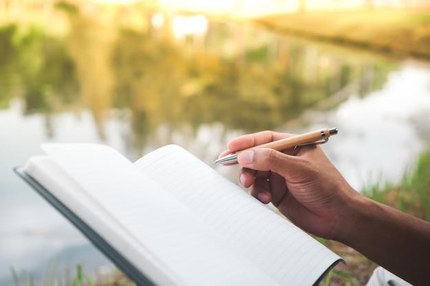 Kobiety ręka spisuje w małym białym notatniku dla notatek, aby nie zapomnieć lub zrobić listę planów.
