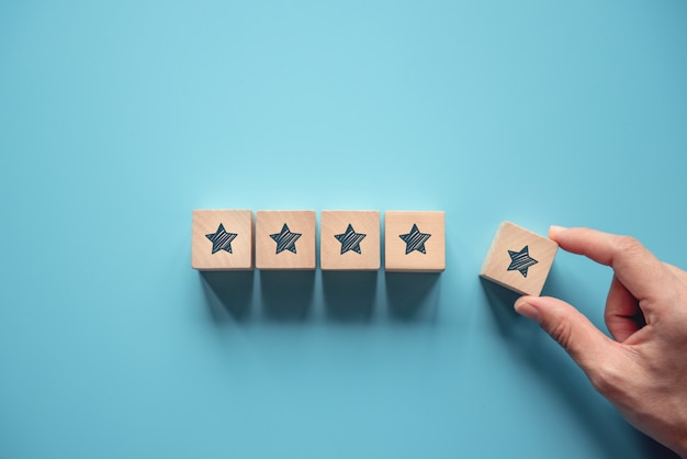 Kobiety ręka stawia drewnianego pięć gwiazdowego kształt na błękitnym tle. najlepsze doskonałe usługi ocena koncepcji doświadczenia klienta, zadowolenie.