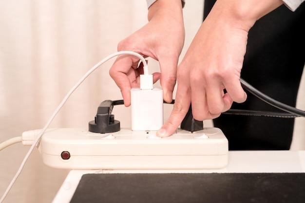 Kobiety ręka stawia elektryczną prymkę podczas włączać onelectricity źródło zasilania