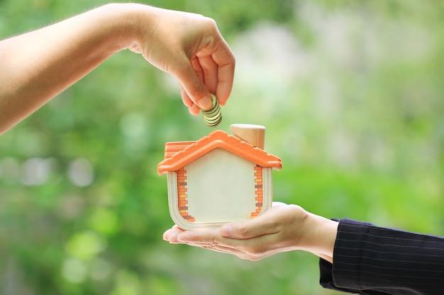 Kobiety ręka stawia monetę w drewnianego dom na naturalnym zielonym tle