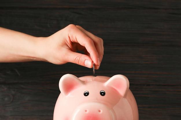 Kobiety ręka stawia monetę w szczęśliwym prosiątko banku na drewno stole przeciw drewnianemu tłu