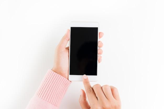 Kobiety ręka trzyma białego telefon komórkowego na bielu stołu tle.