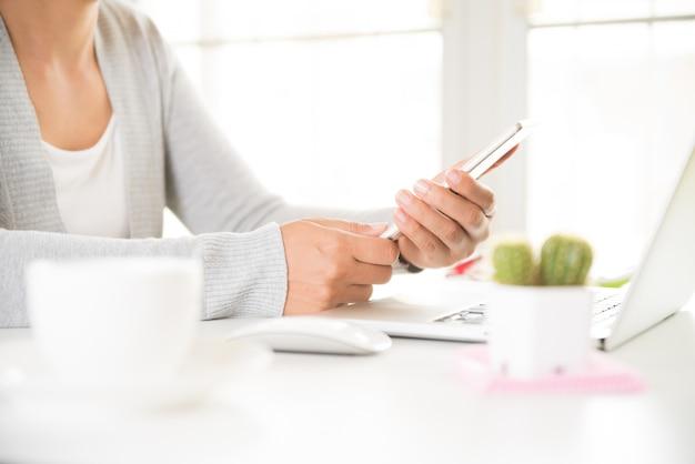 Kobiety ręka trzyma białego telefon komórkowego na stole z laptopem w biurze.