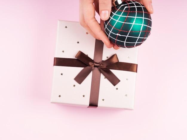 Kobiety ręka trzyma bożego narodzenia cacko. pudełko na prezent