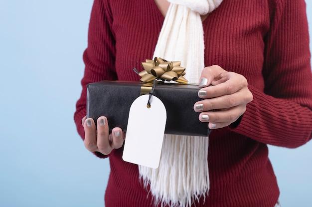 Kobiety ręka trzyma czarnego prezenta pudełko i papierową etykietkę odizolowywająca na białym tle dla bożych narodzeń i nowego roku pojęcia.