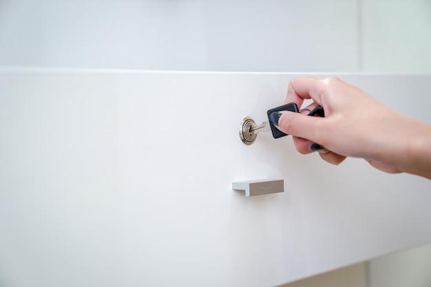 Kobiety ręka trzyma czarny prosty klucz, aby otworzyć białą szafę. wyczyść tło.