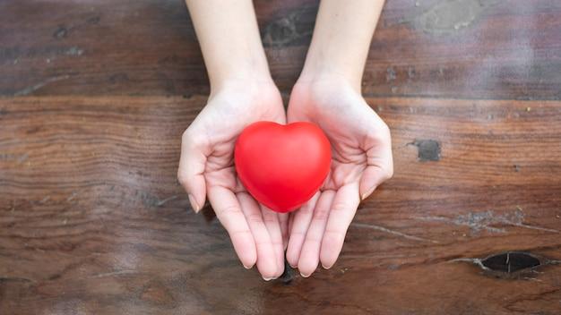 Kobiety ręka trzyma czerwonego serce