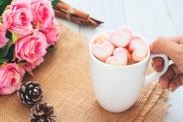 Kobiety ręka trzyma gorącą czekoladę z różowymi marshmallows na wierzchołku. miłość, piękno, walentynki