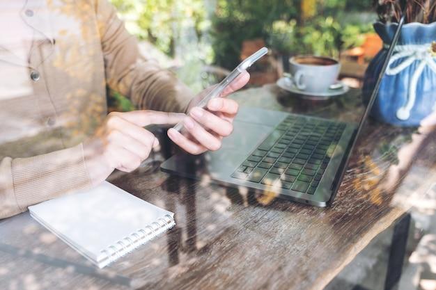 Kobiety ręka trzyma i patrzeje mądrze telefon podczas gdy używać laptop w kawiarni